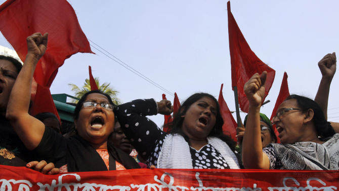 """Bangladeshi garment workers shout slogans as they participate in a protest to mourn the death of the victims of a fire in a garment factory in Dhaka, Bangladesh, Friday, Nov. 30, 2012. Hundreds of garment workers protested Friday outside the Bangladeshi factory where 112 people were killed by the fire, demanding compensation for their lost salaries. The banner reads: """"We demand financial help for the workers."""" (AP Photo/Pavel Rahman)"""