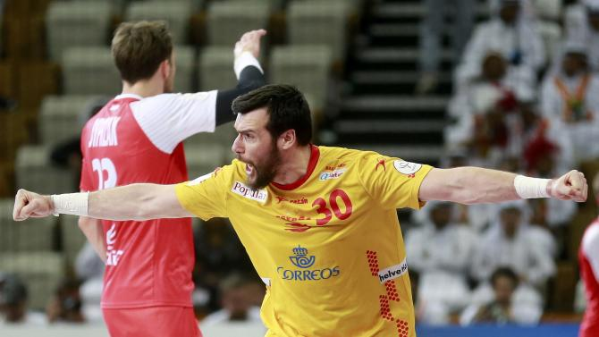 Guardiola of Spain celebrates a goal past Syprzak of Poland during their third-place match of the 24th Men's Handball World Championship in Doha