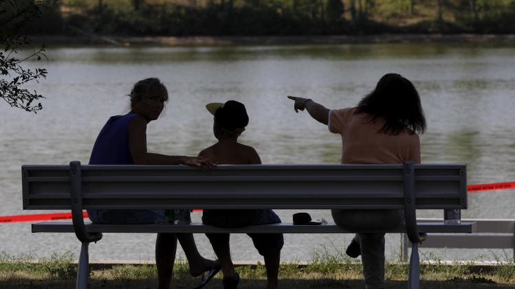 Local residents sit on a park bench near Meyers Lake where Lyric Cook-Morrissey, 10, and Elizabeth Collins, 8, disappeared last Friday, on Tuesday, July 17, 2012, in Evansdale, Iowa. The girls' bikes were found Friday afternoon near a bike trail at the edge of the lake. (AP Photo/Charlie Neibergall)