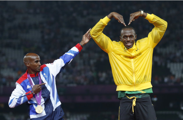 Jamaica's Bolt celebrates with Britain's Farah on the podium after each receiving gold medals, Bolt for men's 4x100m relay and Farah for men's 5000m at the victory ceremony at the London 2012 Olympic 