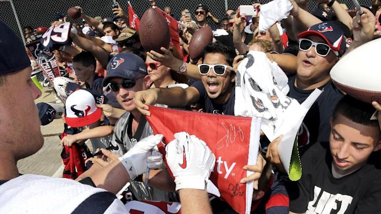 10ThingstoSeeSports - Fans scream as Houston Texans defensive end J.J. Watt, left, signs autographs after an NFL football training camp practice Thursday, Aug. 14, 2014, in Houston