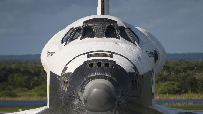 This photo provided by NASA shows a worker at NASA's Kennedy Space Center photographing the space shuttle Endeavour from a hatch on the Shuttle Carrier Aircraft, or SCA, at the Shuttle Landing Facility on Tuesday, Sept. 18, 2012 in Cape Canaveral, Fla. The SCA, a modified 747 jetliner, will fly Endeavour to Los Angeles where it will be placed on public display at the California Science Center. This is the final ferry flight scheduled in the Space Shuttle Program era. (AP Photo/NASA, Bill Ingalls)