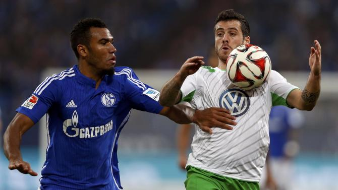 Wolfsburg's Vierinha is challenged by Schalke 04's Choupo-Moting during their German first division Bundesliga soccer match in Gelsenkirchen