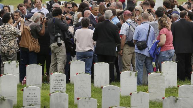 Visitors to Section 60 of Arlington National Cemetery gather around President Barack Obama, center, during his visit there Memorial Day Monday, May 27, 2013, in Arlington, Va. Iraq and Afghanistan war veterans are buried in Section 60. (AP Photo/Pablo Martinez Monsivais)