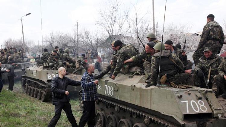 Pro-Russian activists block a collumn of Ukrainian men riding on armoured vehicles in the eastern city of Kramatorsk, on April 16, 2014
