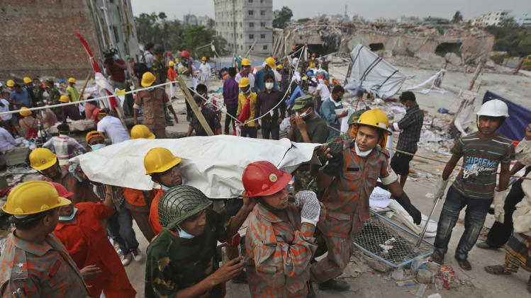 Bangladeshi rescue workers carry the body of a dead garment worker after it was retrieved from a building that collapsed on Wednesday in Savar, near Dhaka, Bangladesh, Sunday, April 28, 2013. Bangladesh rescuers on Sunday located nine people alive inside the rubble of the multi-story building, as authorities announced they will now use heavy equipment to drill a central hole from the top to look for survivors and dead bodies. (AP Photo/Kevin Frayer)