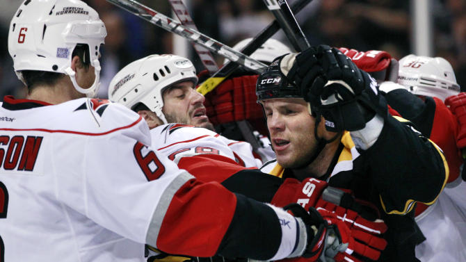 Boston Bruins right wing Shawn Thornton, right, fights with Carolina Hurricanes right wing Chad LaRose, center, and defenseman Tim Gleason (6) in the second period of an NHL hockey game Tuesday, Oct. 18, 2011, in Boston. (AP Photo/Elise Amendola)