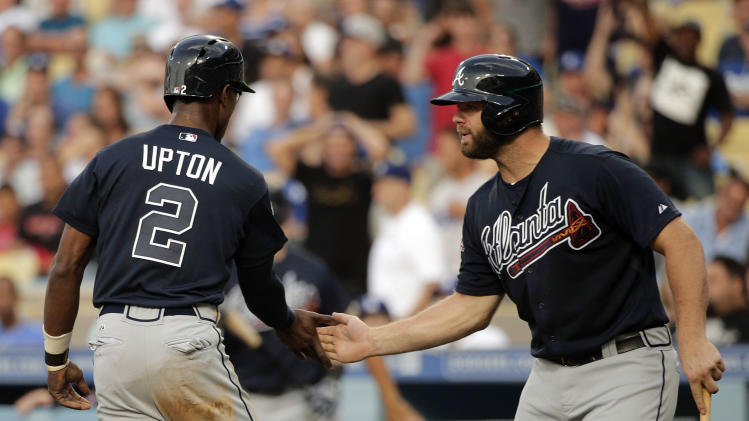 Atlanta Braves' B.J. Upton, left, is congratulated by Evan Gattis after he scored on a sacrifice fly hit by Justin Upton during the first inning of a baseball game against the Los Angeles Dodgers on Tuesday, July 29, 2014, in Los Angeles. (AP Photo/Jae C. Hong)