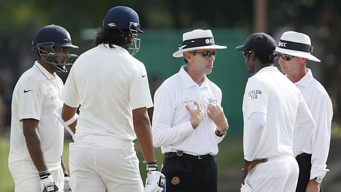 Umpire Llong talks to Sri Lanka's captain Mathews after an argument between India's batsman Sharma and Sri Lanka's bowler Prasad during the fourth day of their third and final test cricket match in Colombo