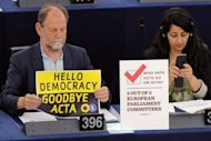 A eurodeputy holds a placard reading &quot;Hello democracy, goodbye ACTA&quot; as members of the European Parliament take part in a vote on Anti-Counterfeiting Trade Agreement (ACTA) at the European Parliament in Strasbourg, eastern France, on Wednesday. The European parliament threw out the controversial global pact to battle counterfeiting and online piracy, quashing any EU ratification