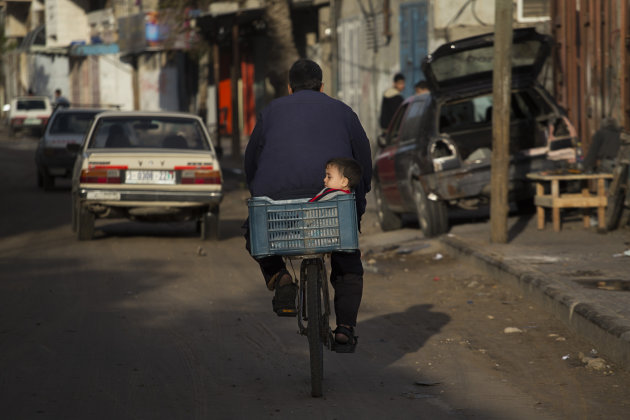 A Palestinian family rides a bike along a street of Gaza City, Sunday, Nov. 25, 2012. A leading Islamic cleric in the Gaza Strip has ruled it a sin to violate the recent cease-fire between Israel and