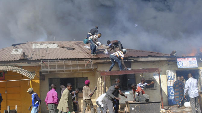 Men struggle to put out the flames as a fire engulfs an auto parts market in Kaduna, Nigeria on Wednesday, Dec. 7, 2011. Emergency officials say at least seven people died in the explosion Wednesday morning in the central Nigerian city that straddles the divide between the country's largely Christian south and Muslim north. Police said they continued to investigate the blast. (AP Photo/Emma Kayode)