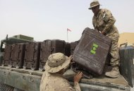 FILE - In this Saturday, July 16, 2011 file photo Canadians soldiers load baggage on the back of a truck at Kandahar airbase in Afghanistan. Canada withdrew 2,850 combat forces from Afghanistan this summer; (AP Photo/Rafiq Maqbool/file)