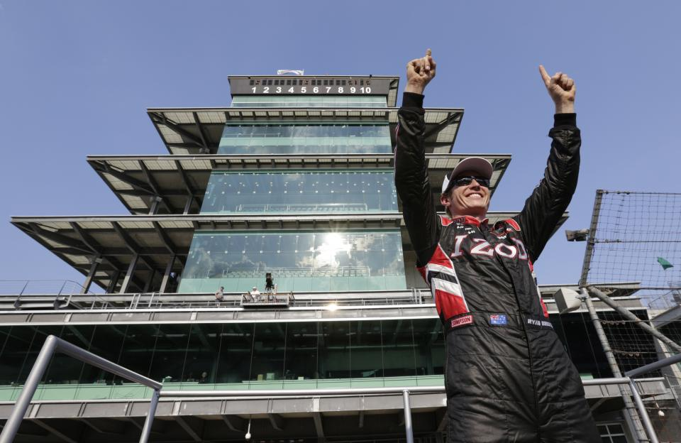 IndyCar driver Ryan Briscoe, of Australia, poses in front of the Pagoda after winning the pole on the first day of qualifications for the Indianapolis 500 auto race at the Indianapolis Motor Speedway in Indianapolis, Saturday, May 19, 2012. (AP Photo/AJ Mast)