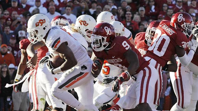 Oklahoma State running back Joseph Randle heads into the end zone with a touchdown in front of Oklahoma defensive back Gabe Lynn (9) during the second quarter of an NCAA college football game in Norman, Okla., Saturday, Nov. 24, 2012. (AP Photo/Sue Ogrocki)