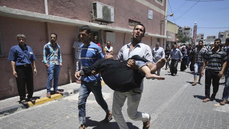 Palestinian man rushes a woman, who medics said was wounded by an Israeli air strike, into a hospital in Khan Younis in the southern Gaza Strip