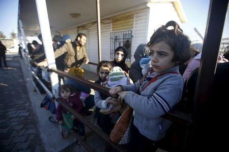 Syrians line up as they wait to cross into Syria at Oncupinar border crossing in the southeastern city of Kilis
