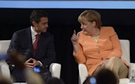 Mexican President Enrique Pena Nieto (L) and German Chancellor Angela Merkel chat during the Business Meeting being held in Santiago on January 26, 2013. Leaders of crisis-hit Europe are meeting their counterparts from resource-rich Latin America in Santiago Saturday to press for closer trade ties to spur global growth