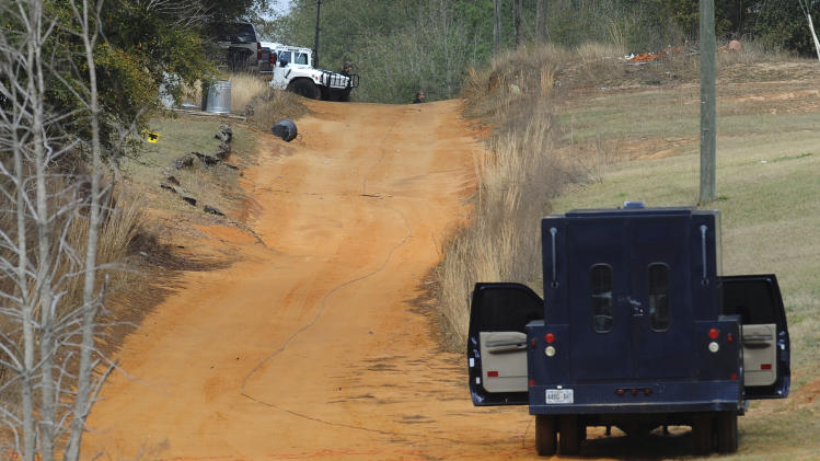 Police vehicles are staged near where a gunman has positioned himself below ground with a child hostage, in Midland City, Ala. on Wednesday Jan. 30, 2013. Authorities were locked in a standoff Wednesday with a gunman authorities say on Tuesday intercepted a school bus, killed the driver, snatched a 6-year-old boy and retreated into a bunker at his home in Alabama. (AP Photo/Montgomery Advertiser, Mickey Welsh)