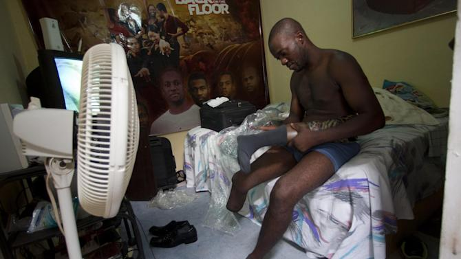 In this July 20, 2012 photo, professional dancer Georges Exantus prepares to put on his prosthetic limb in his bedroom as he prepares for his wedding in Port-au-Prince, Haiti.  Exantus thought he'd never dance again.  The earthquake three years ago in Haiti's capital flattened the apartment where he was living, where he spent three days trapped under a heap of jagged rubble. After friends dug him out, doctors amputated his right leg just below the knee. Israeli doctors and physical therapists who came to Haiti after the quake sent him to Israel for surgery and rehabilitation. Three years later, the 32-year-old professional dancer is back on the floor, spinning away as he does the salsa, cha-cha and samba. (AP Photo/Dieu Nalio Chery)