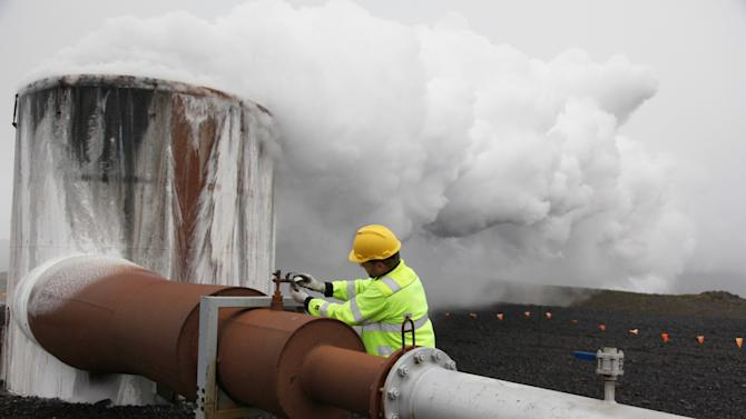 In this July 28, 2011 photo, Bergur Sigfusson, the CarbFix experiment's technical manager, checks a valve at a test well at Reykjavik Energy's Hellisheidi geothermal power plant in Iceland. CarbFix's scientists will separate carbon dioxide from the volcanic field's steam and pump it underground to react with porous basalt rock, forming limestone, to see how well the gas most responsible for global warming can be locked away in harmless form. (AP Photo/Brennan Linsley)