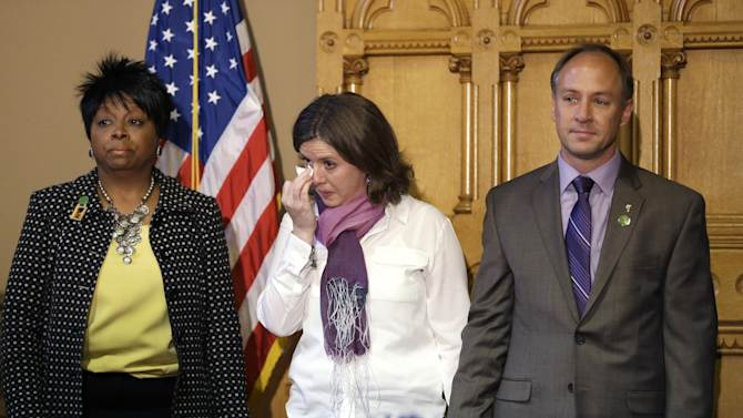 CORRECTS FIRST NAME OF FATHER TO MARK BARDEN INSTEAD OF DANIEL BARDEN - Jackie and Mark Barden, parents of Sandy Hook shooting victim Daniel Barden, center and right respectively, react while holding hands and standing next to Deborah Davis, left, who lost her son to gun violence in 2010, during a legislation signing ceremony at the Capitol in Hartford, Conn., Thursday, April 4, 2013. The legislation signed by Conn. Gov. Dannel P. Malloy brings into law new restrictions on weapons and large capacity ammunition magazines, a response to last year's deadly school shooting in Newtown. (AP Photo/Steven Senne)