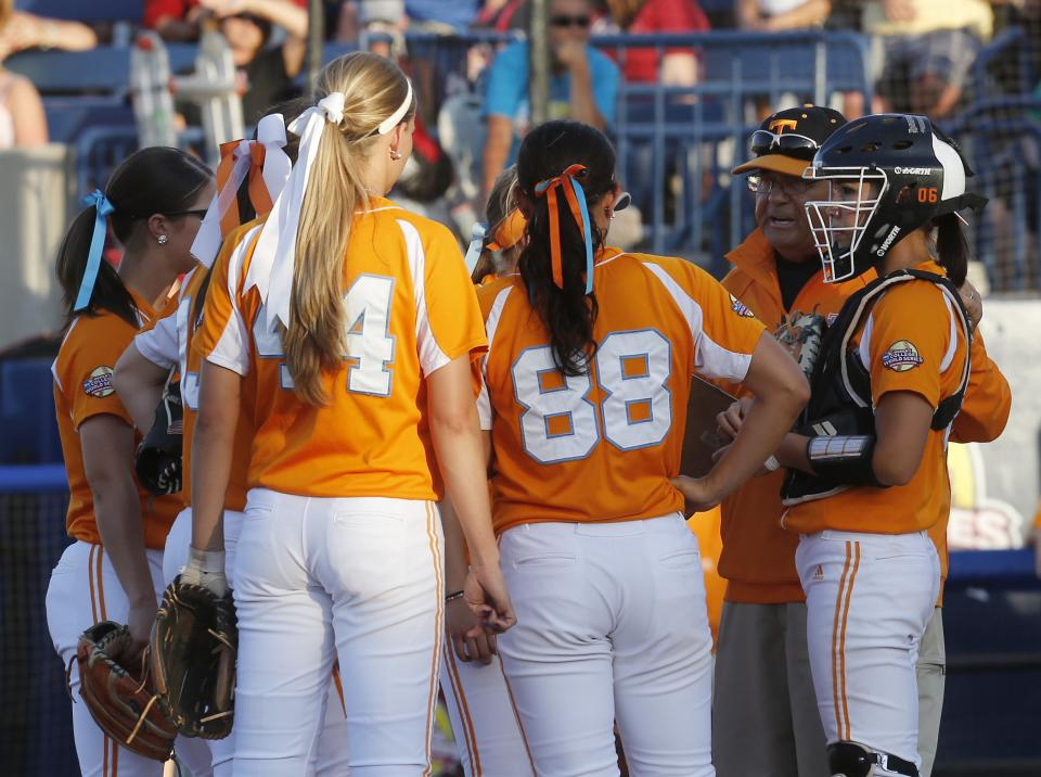Tennessee co-head coach Ralph Weekly, second from right, goes out to the pitchers circle to talk to his team during the third inning of the first game of the best of three Women's College World Series NCAA softball championship series against Oklahoma in Oklahoma City, Monday, June 3, 2013. (AP Photo/Sue Ogrocki)