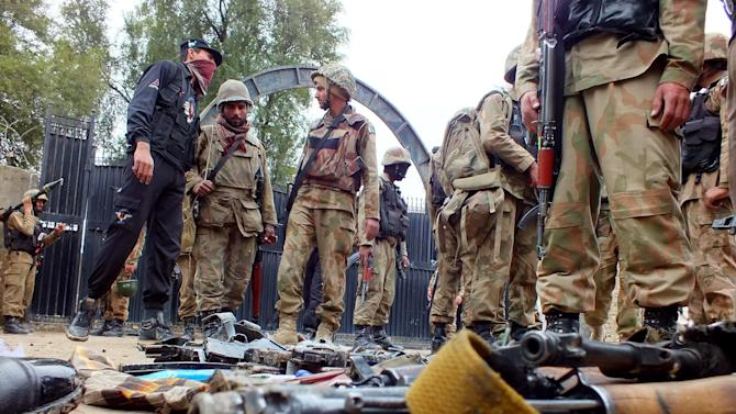 Pakistan army soldiers stand inside the police station attacked by militants in Bannu, Pakistan on Thursday, Feb. 14, 2013. Five suicide bombers attacked a police station in the country's northwestern city of Bannu, wounding a police officer. The city's police chief Nisar Tanoli said three of the bombers detonated their explosives vests while the police shot dead the other two. (AP Photo/Jibran Yousufzai)