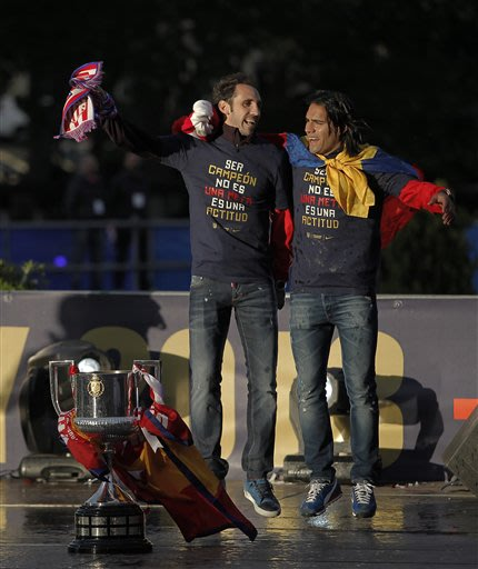 Atletico de Madrid's Radamel Falcao from Colombia, right, and Diego Godin from Uruguay, left, celebrate in Neptuno Square in Madrid, Spain, Saturday, May 18, 2013. Atletico de Madrid defeated Real Mad