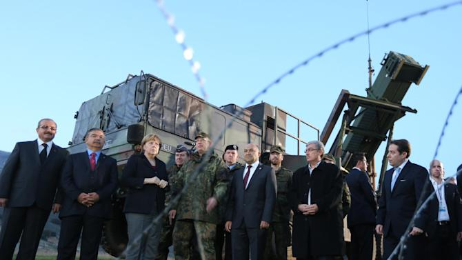 German chancellor  Angela Merkel , third left, stands in front of  an army vehicle, part of a Patriot surface-to-air missile system during her visit to  Kahramanmaras, southeastern Turkey Sunday Feb. 24, 2013. German Chancellor Angela Merkel is visiting German troops deployed to operate Patriot missile batteries in Turkey. The Patriots were sent to Turkey, a NATO member, to protect it from spillover from Syria's civil war. Merkel's two-day visit comes as Turkey grows increasingly frustrated over the slow progress in its bid for European Union membership. Before arriving Sunday, Merkel said she backs opening a new chapter in those stalled talks, despite being skeptical about Turkey's accession.  The chancellor's first stop was Kahramanmaras, some 100 kilometers (60 miles) from the Syrian border, where some 300 German troops are manning two out of six NATO-deployed anti-missile batteries.    (AP Photo/dpa, Kay Nietfeld)