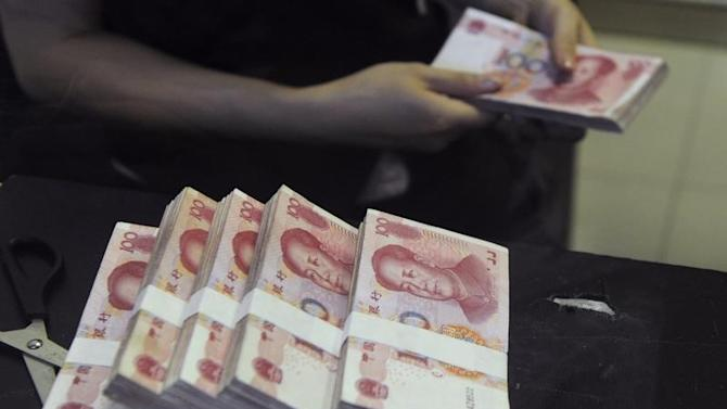An employee counts Chinese 100 yuan banknotes at a branch of China Merchants Bank in Hefei