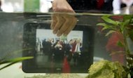 A waterproof tablet PC from Fujitsu is lowered into a fish tank at CeBIT, the world&#39;s biggest high-tech fair in Hanover, Germany, on March 6, 2012. Water-powered clocks, eye-controlled arcade games and pole-dancing robots: this year&#39;s CeBIT tech fair, the world&#39;s biggest, showcased gadgets ranging from the useful to the downright nerdy