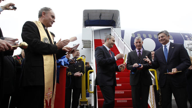 Fr. Stanislaw Michalek, left, looks on as LOT Polish Airlines executive Tomasz Balcerzak, center, shakes hands with Boeing executives Ray Conner, right, and Larry Loftis in front of a Boeing 787 during a delivery ceremony Wednesday, Nov. 14, 2012, at Paine Field in Everett, Wash. LOT Polish Airlines took delivery of its first Boeing 787 and plans to fly early next year on routes between Poland and New York, Chicago and Toronto. Poland's LOT was Europe's first airline to purchase the new plane with an order for eight. Boeing says the 787 is the first mid-size plane capable of flying long-range routes, allowing airlines to open new, non-stop flights. (AP Photo/Elaine Thompson)