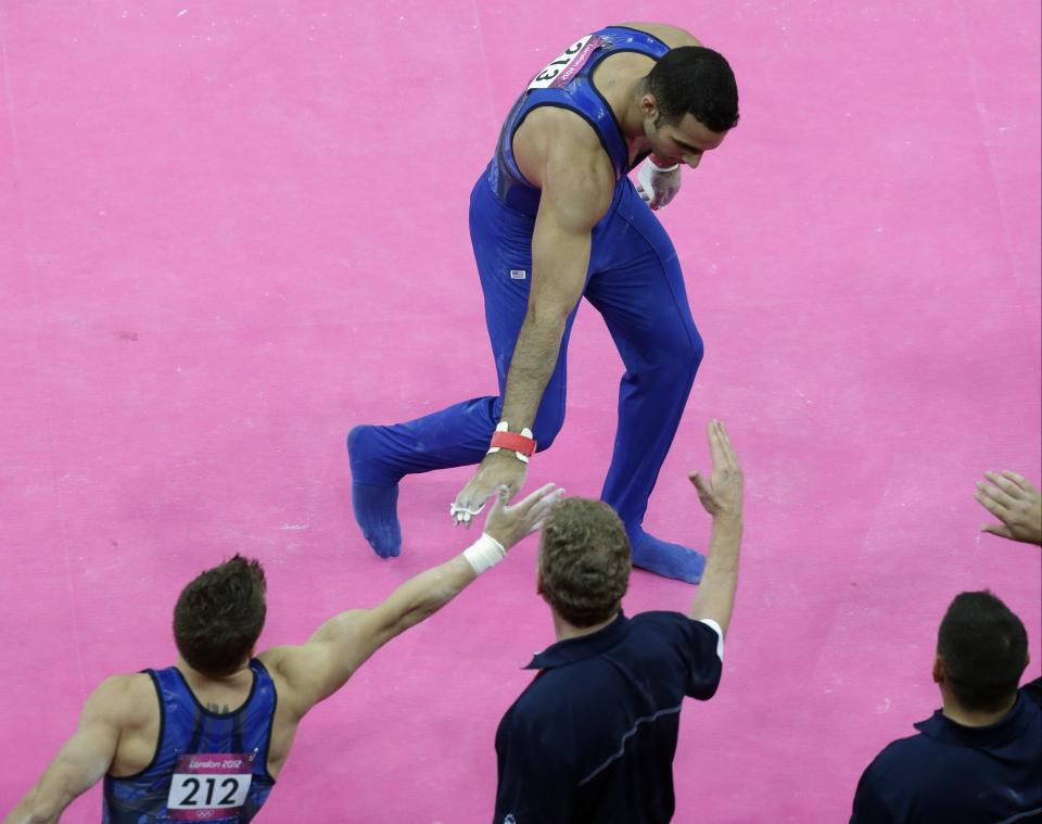 U.S. gymnast Danell Leyva greets members of his team after a performance during the Artistic Gymnastics men's qualification round at the 2012 Summer Olympics, Saturday, July 28, 2012, in London. (AP Photo/Julie Jacobson)