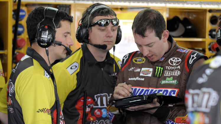 Kyle Busch, right, and crew members look over a tablet during practice for the NASCAR Sprint All-Star auto race at Charlotte Motor Speedway in Concord, N.C., Friday, May 17, 2013. (AP Photo/Mike McCarn)