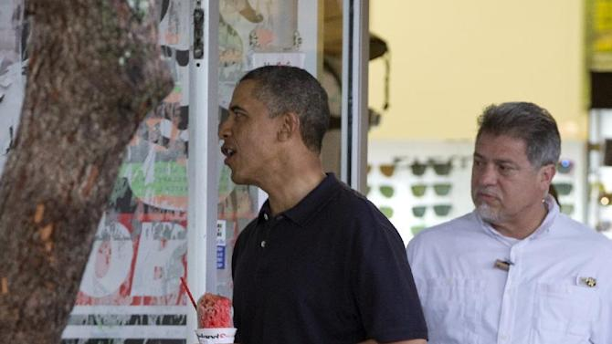 President Barack Obama holds his shave ice as he exits Island Snow to greet people waiting outside, Thursday, Jan. 3, 2013, in Kailua, Hawaii. President Obama and the first family are in Hawaii for a holiday vacation. (AP Photo/Carolyn Kaster)