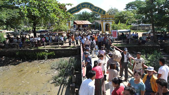 In this photo taken on Nov. 8, 2012, policemen stand guard as passengers arrive at a jetty in Mrauk-U, Rakhine state, western Myanmar. Mrauk-U itself has been spared the bloodshed between the Buddhist Rakhine and the Muslim Rohingya that has scarred other parts of Rakhine state. It is calm, and for foreign tourists, safe. But just 10 kilometers (six miles) to the south, there is a village where civilians were reportedly beheaded in a massacre last month that saw women and children slaughtered, then buried in mass graves. Across western Myanmar's Rakhine state, the United Nations is distributing emergency supplies of food and shelter to terrified villagers who have fled burning homes. A nighttime curfew is in force. (AP Photo/Khin Maung Win)