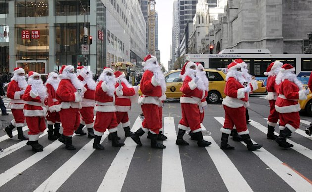 Volunteers of America Santas ring their bells as the cross a street in Fifth Ave. during their 110th annual Sidewalk Santa Parade, in New York,  Friday, Nov. 23, 2012. The donations they raise are use