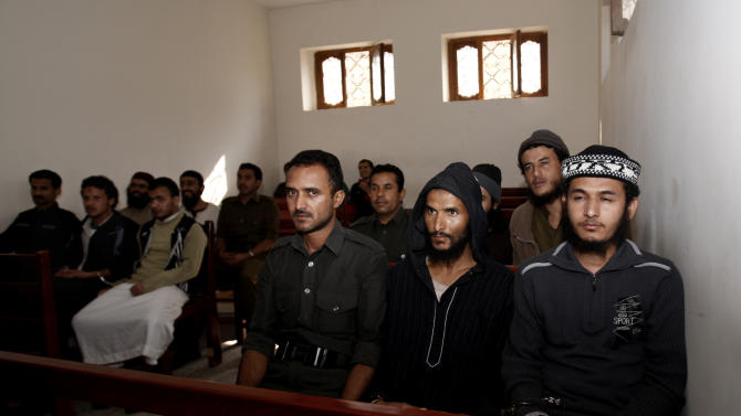 A Yemeni soldier, center, sits with suspected al-Qaida militants during their trial at a state security court in Sanaa, Yemen, Sunday, Jan. 6, 2013. Yemen's state security court has sentenced five alleged al-Qaida militants to up to 10 years in prison for carrying out attacks against security forces and supporting the group logistically in the southern province of Abyan in 2011. (AP Photo/Hani Mohammed)