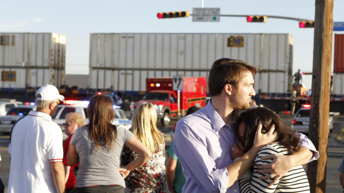 FILE - In this Nov. 15, 2012, file photo bystanders react as emergency personnel respond to an accident after a parade float carrying veterans was struck by a train in Midland, Texas, killing four veterans and injuring sixteen others. The driver of a parade float told National Transportation Safety Board investigators in documents released Wednesday, May 22, 2013, that the oncoming train appeared stationary to him. (AP Photo/Reporter-Telegram, James Durbin, File)