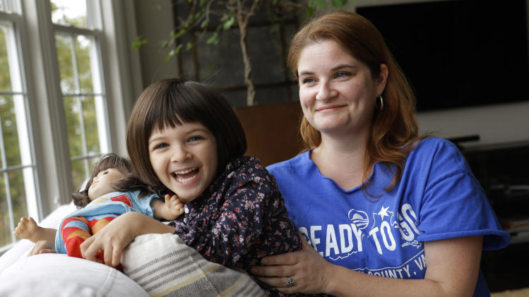 "In this Monday, Oct. 8, 2012 photo, Molly Lovato, a volunteer with the Obama campaign, poses for a photograph with her daughter Nola Trindade, 4, at their home in Leesburg, Va. Lovato credits the president with steering the country away from financial disaster. ""I think he kept us from sliding into a depression,"" she says. ""I'm really dumbfounded by people who say 'Why didn't he fix this?' and it's 20 minutes later."" She compares reviving the economy to gutting and then rehabbing a home. ""It takes a hot minute for everything to unravel,"" she says, ""but to put it back together is really very difficult."" (AP Photo/Jacquelyn Martin)"