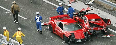 Police officers investigate damaged Ferrari cars at the site of a traffic accident on the Chugoku Expressway in Shimonoseki, southwestern Japan, Sunday, Dec. 4, 2011. (AP Photo/Kyodo News)