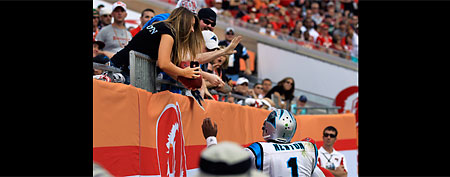 This photo made Dec. 4, 2011 shows Carolina Panthers quarterback Cam Newton (1) handing 16-year-old Katie Brown the football after scoring his record-setting 13th rushing touchdown against the Tampa Bay Buccaneers during the fourth quarter of an NFL football game, in Tampa, Fla. Brown was stunned when Newton handed her the game ball. She was even more suprised when the team's equipment staff came to retrieve it. (AP Photo/Chris O'Meara)