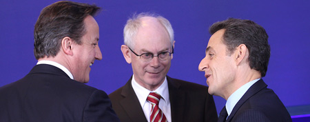 British Prime Minister David Cameron (left) touches the arm of French President Nicolas Sarkozy as they speak with European Council President Herman Van Rompuy during a group photo at an EU summit in Brussels on Friday. (AP Photo/Yves Logghe)