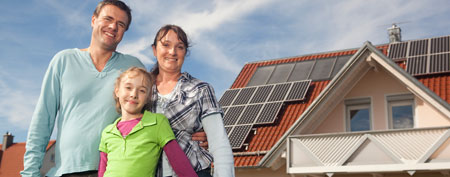 Family in front of home with solar panels. (StockByte)