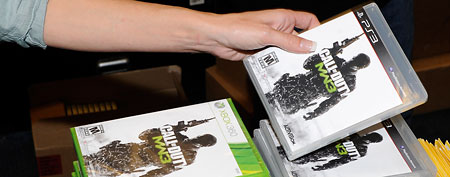 "GameStop employee Randi Taber rings up copies of ""Call of Duty: Modern Warfare 3"".  (Photo by Ethan Miller/Getty Images)"