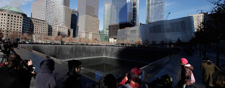 Visitors walk around the National September 11 Memorial, Thursday, Dec. 29, 2011 in New York. The museum entrance is at right. (AP Photo/Mark Lennihan)