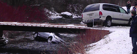 In this Saturday, Dec. 31, 2011 photo provided by rescuer Chris Willden, a car is submerged in the icy Logan River near Logan, Utah, after as many as 10 passersby jumped in to flip it back over and rescue three young children trapped inside. (AP Photo/Chris Willden)