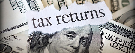 Tax return with hundred dollar bills (Thinkstock)