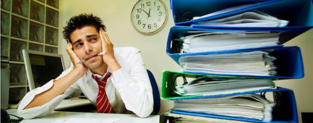 Overwhelmed man at work (ThinkStock)